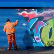 Graffiti-Entfernung von blauem Metalltor
